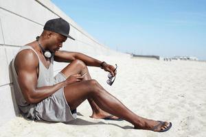 ung afrikansk kille som skickar ett textmeddelande på stranden
