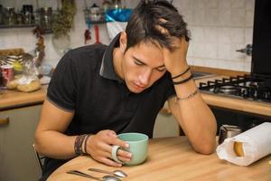 trött man med kaffesammanträde vid köksbordet foto