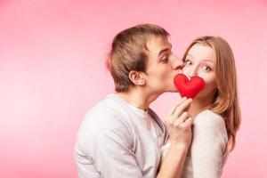 man kyssande flicka gömmer sig bakom ett litet rött hjärta foto