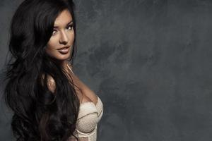 trendig ung brunett sensuell kvinna poserar. långt lockigt hår. foto