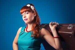 vacker pin-up flicka poserar med vintage resväska mot blå foto
