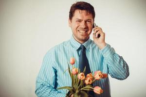 affärsman som ler medan du ringer och håller tulpaner foto