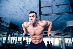 ung muskulös man träning på barer foto