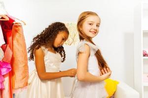 afrikansk flicka hjälper en annan att passa vit klänning foto