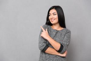 leende kvinna som pekar fingret bort foto