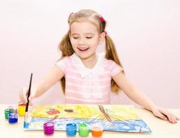 söt leende liten flickateckning med målarfärg och pensel foto