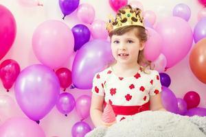 söt flicka poserar i krona på ballonger bakgrund foto