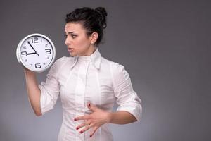 porträtt av trevlig tjej som håller en stor klocka i hennes händer foto
