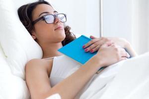 vacker ung kvinna som sover efter att ha läst en bok. foto