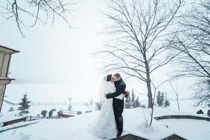 bruden och brudgummen som går på staden i snön foto