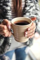 flickans händer som håller en kopp kaffe foto