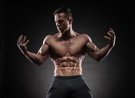 muskulös kille på svart bakgrund foto