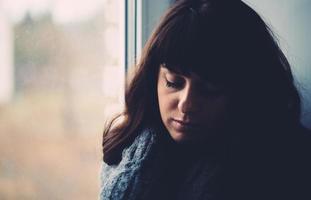 ung kvinna längtar nära ett fönster