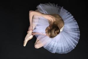 ung balettdansare som binder pointe som sitter på golvet foto