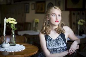 vacker ung kvinna som väntar vid ett bord i gamla kafé. foto