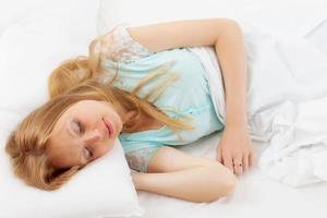 långhårig kvinna som sover i sängen foto