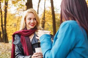 två kvinnor som dricker kaffe i parken foto