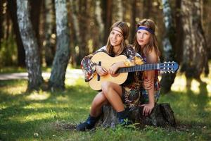 två hippiflickor med gitarr i en sommarskog
