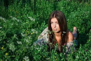 trevlig tjej bland grönt gräs och blommor foto