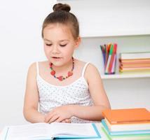 söt flicka läser bok foto