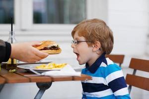 liten pojke som äter snabbmat: pommes frites och hamburgare foto