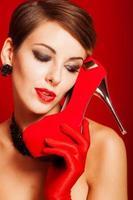 vacker flicka med en röd sko foto