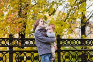 bror och babysyster som går i en höststadspark