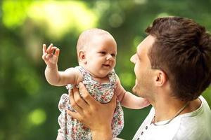 pappa och nyfödda dotter som leker i parken i kärlek foto