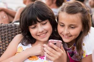 två flickor med leende för smartphone