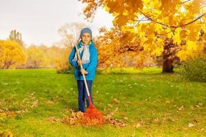 pojke i blå jacka med rake rengöringsgräs foto