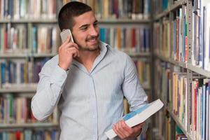 manlig student som pratar i telefon i biblioteket foto