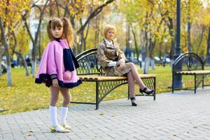 söt liten flicka i höst park foto