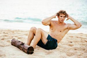 man gör sit-ups utomhus på stranden foto