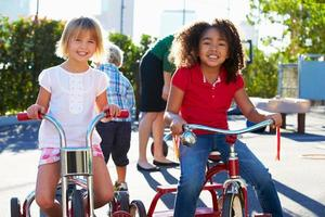 två flickor som cyklar med trehjulingar på lekplatsen foto