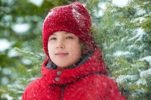 lycklig pojke med fallande snö i skogen foto