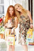 två attraktiva glada tjejer ute och shoppar foto