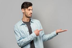 stilig ung man som pekar på något foto
