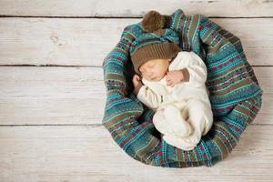 nyfött barn som sover i stickad ullhatt, träbakgrund foto