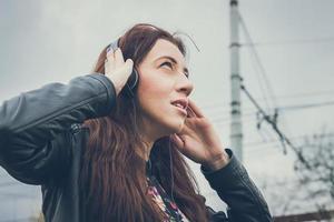 vacker flicka med långt hår lyssnar på musik