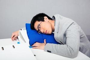 ung affärsman sleepig på bordet foto