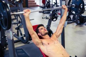 man träning med skivstång på bänken på gymmet foto