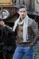 stilig ung man i skinnjacka och jeans. gammalt tåg foto