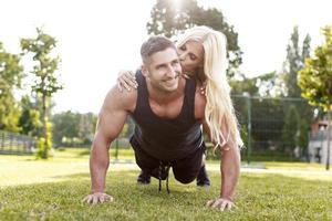 fit man gör armhävningar med kvinnan på ryggen foto