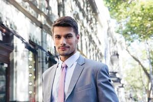 porträtt av en stilig affärsman i kostym utomhus foto