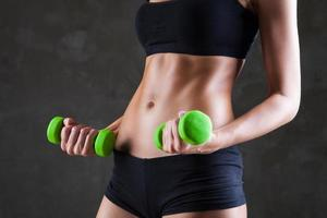 kropp av ung fit kvinna lyfta hantlar