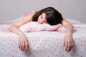 flicka trött på att sova i sängen foto