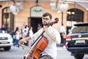 kille som spelar cello på gatan på sommaren foto