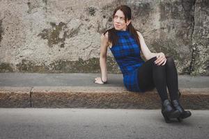 vacker flicka sitter på trottoaren foto