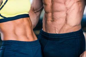 muskulös mans och sportiga kvinnors överkropp foto