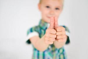 liten pojke som gör tummen för kameran, står hemma foto